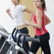 Womanworkout in fitness club on running track machine — Stock Photo