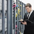 Businessman with laptop in network server room — Stockfoto