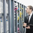 Businessman with laptop in network server room — Stock Photo #4793785
