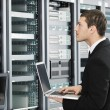 Royalty-Free Stock Photo: Businessman with laptop in network server room