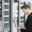 Stock Photo: Businessmwith laptop in network server room