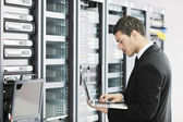 Businessman with laptop in network server room — Photo