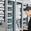 Young it engeneer in datacenter server room - ストック写真