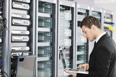 Young it engeneer in datacenter server room — 图库照片
