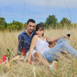 Stock Photo: Happy couple enjoying countryside picnic in long grass