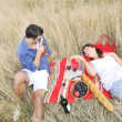 Happy couple enjoying countryside picnic in long grass — Stock Photo #4827834