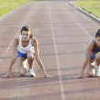Two girls running on athletic race track — Stock Photo
