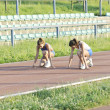 Two girls running on athletic race track - Stock Photo