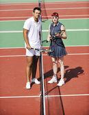 Gelukkige jonge paar spelen tennisspel buiten — Stockfoto