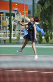 Ung kvinna spela tennisspel utomhus — Stockfoto