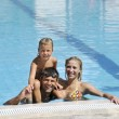 Happy young family have fun on swimming pool — Stock Photo #4980063
