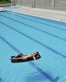 Vacker kvinna koppla av i poolen — Stockfoto