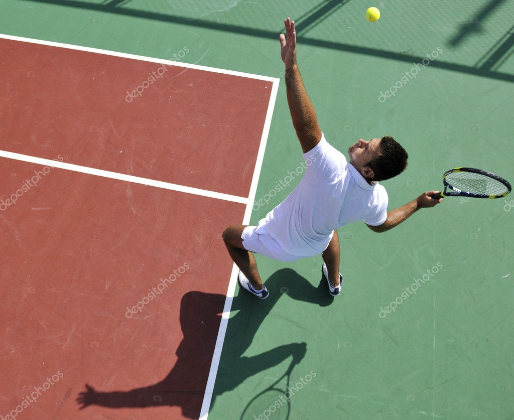 Young man play tennis outdoor on orange tennis court at early morning — Stock Photo #4984829