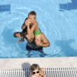 Happy young family have fun on swimming pool — Stock Photo #4994587