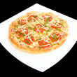 Round pizza on square plate — Stock Photo