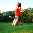 Happy woman jumping on grass — Stock Photo