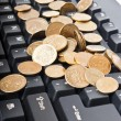 Coins on keyboard - Stock Photo