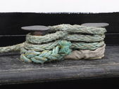 Close up of a rope tied onto cleat dockside — Stock Photo