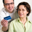 Mature couple shopping online, paying by credit card — Stock Photo #3313660