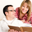 Happy couple reading a book - Stockfoto