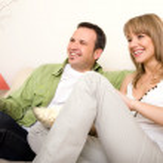Smiling couple watching TV — Stock Photo