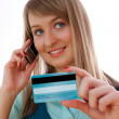 Young woman with credit card and cellphone - Stock Photo