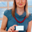 Young woman holding a blank business card - Stock Photo