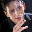 Portrait of young handsome man smoking a cigarette - Photo