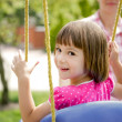 Little girl on a swing, family — Stock Photo