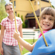 Smiling mother and daughter having fun on playground - Stock Photo