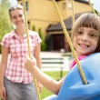 Stock Photo: Smiling mother and daughter having fun on playground