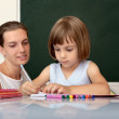 Pupil working at desk under the supervision of a teacher — Stock Photo