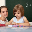 Stock Photo: Elementary school pupil working under supervision of teacher
