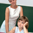 Stock Photo: Pupil working at desk under supervision of teacher