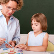 Little girl working under the supervision of a mature teacher — Stock Photo