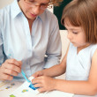 Elementary school pupil working under supervision of educator — Stock Photo #3668816