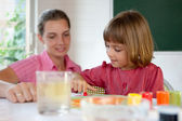 Elementary school pupil painting under the supervision of a teacher — Stock Photo