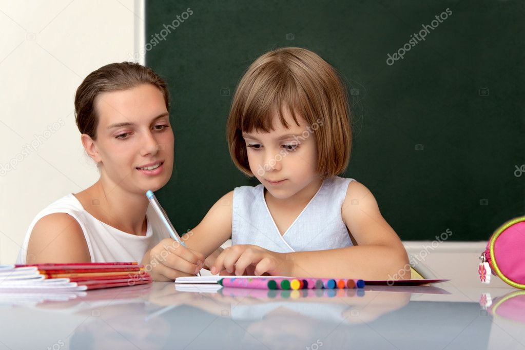 Elementary school pupil working at desk under the supervision of a teacher — Stock Photo #3668790