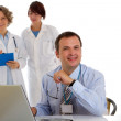 Stock Photo: Portrait of male doctor with two of his co-workers