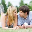 Young happy couple laying on grass - 图库照片