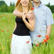 Smiling happy couple in filed of poppy — Stock Photo #2696692