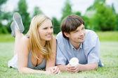 Unga lyckliga par avkopplande på park — Stockfoto