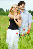 Smiling happy couple in filed of poppy — Stock Photo