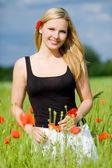 Beautiful woman trough poppy field — Stock Photo