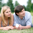 Young happy couple laying on grass — Stock fotografie