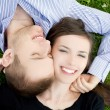 Smiling young couple is cuddle on a gree - Stock Photo