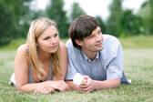 Young happy couple laying on grass — Stock Photo