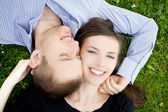Smiling young couple is cuddle on a gree — Stock fotografie