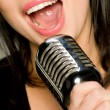Stock Photo: Young Woman Singing into Microphone