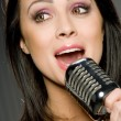 Young Woman Singing into Microphone - Stock Photo